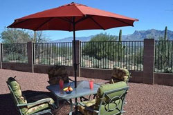 patio/deck with table and chairs for 4 with green seat cushions and large red umbrella open to cover table in shade, beautiful mountain view in the background, mental fence with stone (?) columns, pet friendly vacation home for rent in tucson